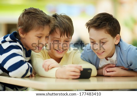 Three boys surfing the net on smartphone - stock photo