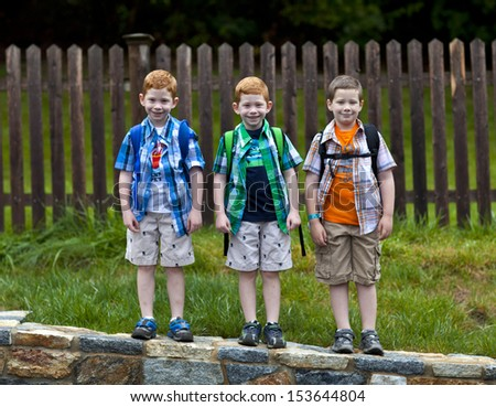 Three boys wearing backpacks ready for school