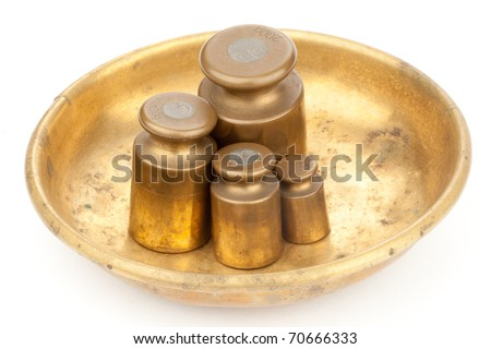 Three brass old weights on a golden plate - stock photo