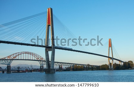 Three bridges crossing the Fraser River, the sky train bridge, the Patullo bridge, and the railway bridge - stock photo