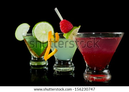 three bright martinis garnished with fresh fruit isolated on a black background