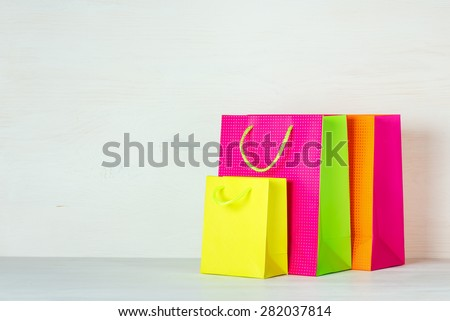Three bright multicolored shopping bags on a white wooden background - stock photo