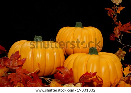 Three bright orange pumpkins arranged together on a black background with some autumn leaves.