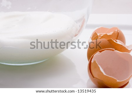 Three broken eggs and a bowl with whisked egg white