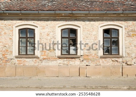 Three broken windows in a wall of a damaged house - stock photo