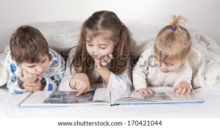 Three brothers boy and two girls lying in bed reading a book - stock photo