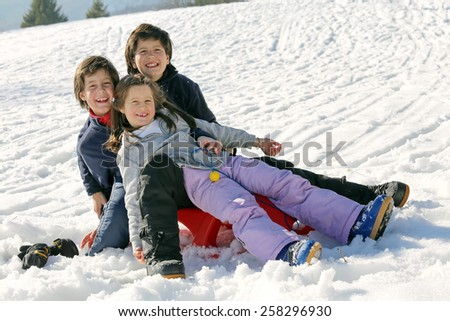 Three brothers on the snow in the mountains in winter - stock photo