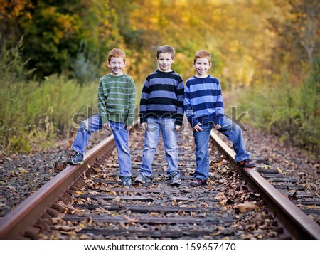 Three brothers standing an old rail tracks