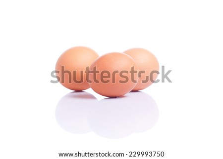 Three brown eggs isolated on white background with reflection side view - stock photo