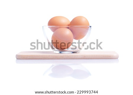 Three brown eggs on a small cutting board isolated on white background with reflection side view - stock photo