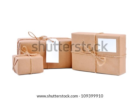 Three brown packages with blank labels on white - stock photo