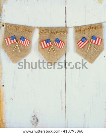 Three burlap pennants with crossed USA toothpick flags hanging from twine in front of white washed rustic wooden background good for United States holidays and events - stock photo