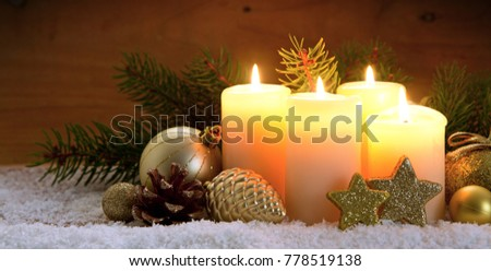 Three burning advent candles and Christmas decoration.