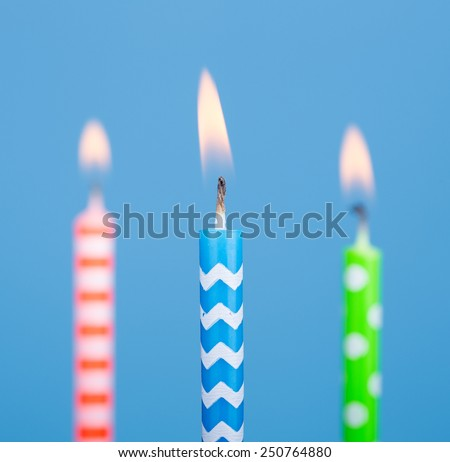 Three burning birthday candles on a blue background - stock photo