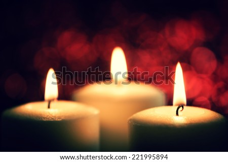 three burning candles on a red background