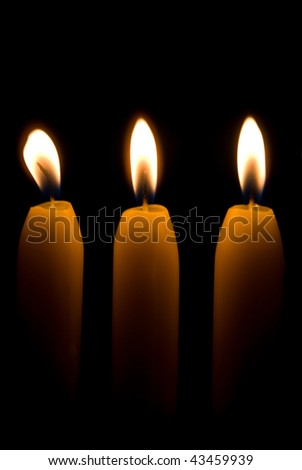 Three burning candles over a black background