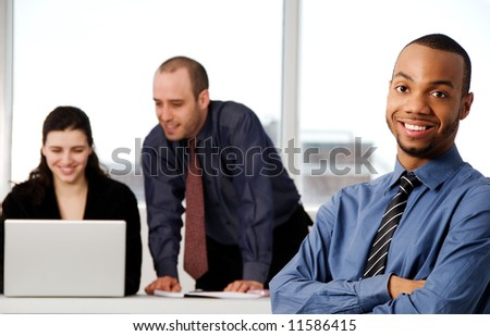 three business associates with a grey laptop - stock photo