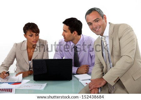 Three business colleagues at a desk - stock photo