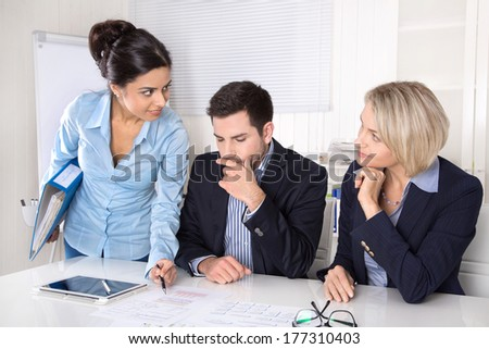 Three business colleagues discussing at desk