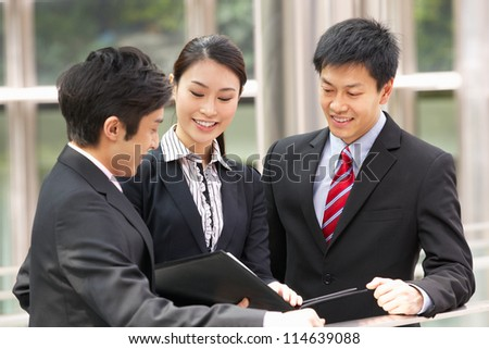 Three Business Colleagues Discussing Document Outside Office - stock photo