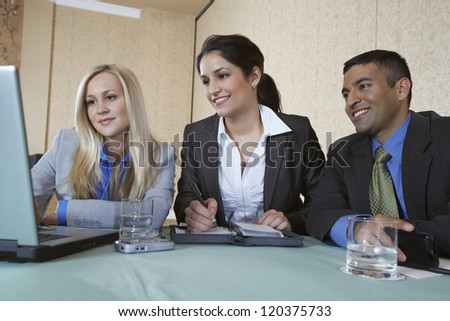 Three Business colleagues looking at laptop while working together