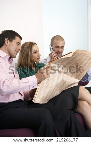 Three business colleagues sitting on sofa, man reading newspaper, second man using mobile phone