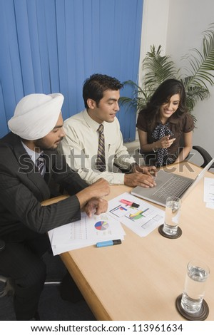 Three business executives having a meeting in an office - stock photo