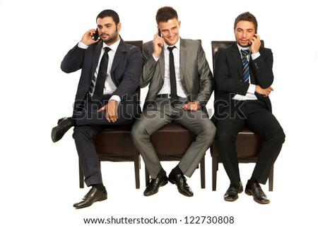Three business men sitting on chairs in a line and speaking by phones mobile isolated on white background - stock photo