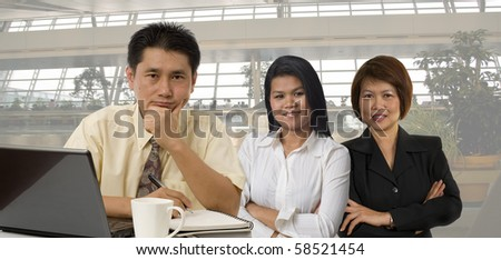 Three business office workers standing together - stock photo