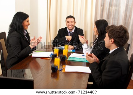 Three business people applauding and congratulate their colleague man - stock photo