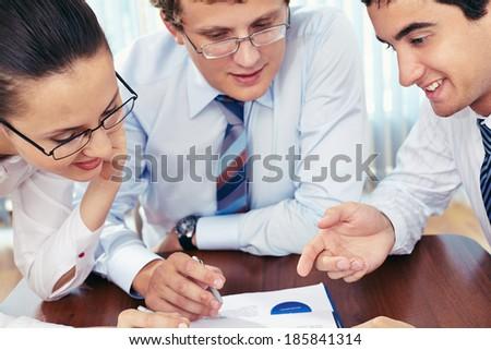 Three business people examining paper - stock photo