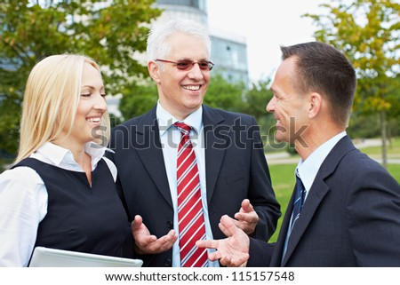 Three business people having a discussion outside in a park - stock photo