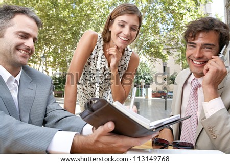 Three business people having a meeting while sitting at a coffee shop terrace outdoors. - stock photo