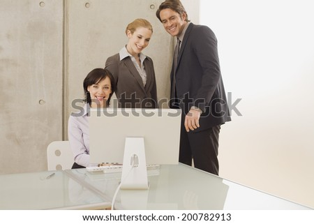 Three business people in office looking at computer