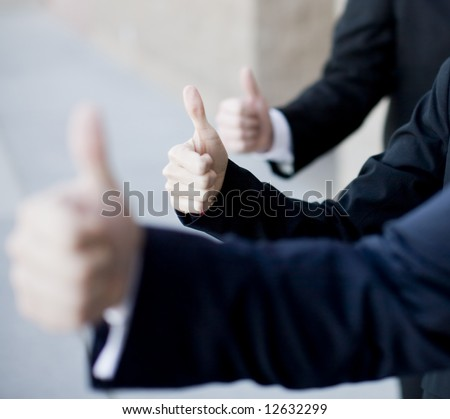 Three business people in suits giving thumbs up