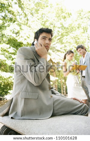 Three business people in the park, meeting and using technology. - stock photo