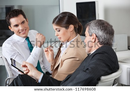 Three business people planning a capital investment in the office - stock photo