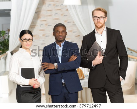 Three business people posing in restaurant. Business people of Caucasian, Korean and Asian origin communicating about business projects and questions.