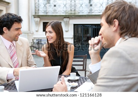 Three business people sharing a table at a coffee shop terrace, having a conversation during a meeting and using technology in the financial city district. - stock photo
