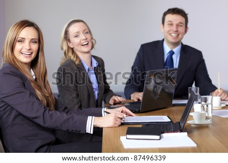 Three business people sitting at conference table and have a laugh - stock photo