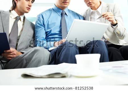 Three business people sitting on sofa and looking at laptop