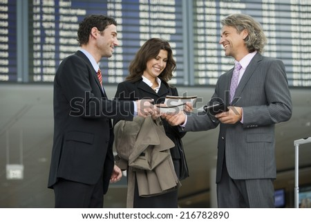 Three business people standing at the airport. - stock photo
