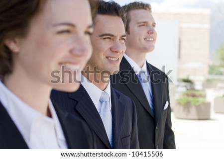 three business people standing in a row looking in same direction - stock photo