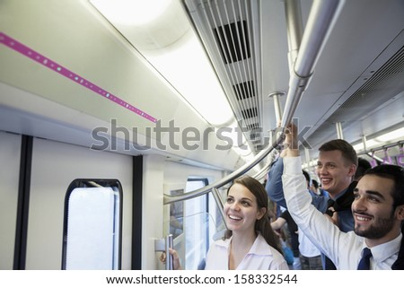 Three business people standing on the subway and looking at the map - stock photo