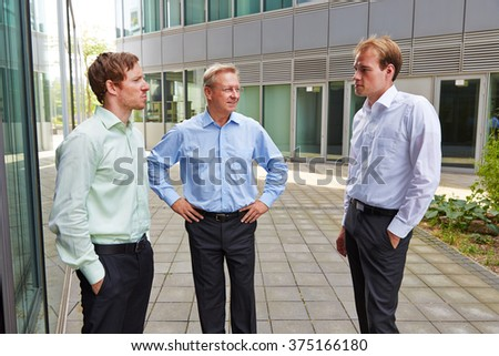 Three business people standing outside and talking during lunch break - stock photo