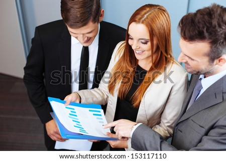 Three business people talking about company performance and analysing chart during meeting