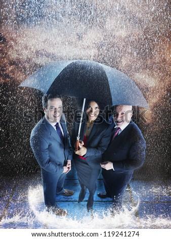 Three business people under one umbrella during rainy season - stock photo