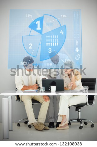 Three business people using blue pie chart interface while working - stock photo