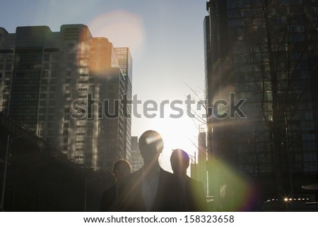 Three business people walking down city street with sunlight at their back