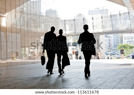 Three business people walking down the street talking. Silhouettes. Motion Blur. - stock photo